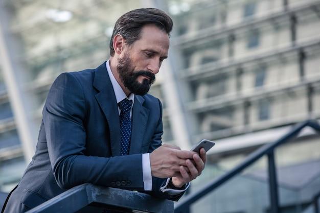 忙しい生活。手すりに寄りかかって電話を持っているひげを生やした集中ビジネスマンの腰