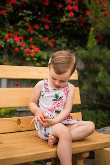 Занятая маленькая девочка в ярком платье сидит на скамейке на фоне цветущей розы