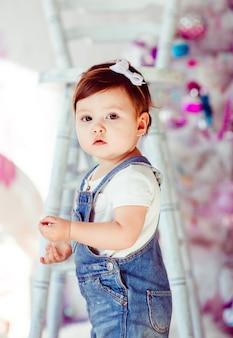 Занятая маленькая девочка в джинсах-джамперах стоит перед высоким белым креслом