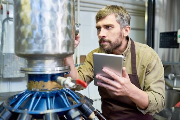 工場で醸造設備を調整する忙しい男性エンジニア