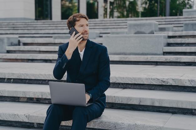 統計データを扱う忙しい男性起業家が携帯電話を介してパフォーマンスについて話し合う