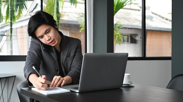 Занят мужчина-предприниматель разговаривает по мобильному телефону и делает заметку на ноутбуке.