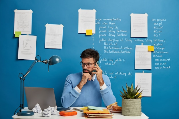 Busy male freelancer in blue outfit, checks information on laptop computer, uses modern cellphone gadget for calling, sits at white table with papers