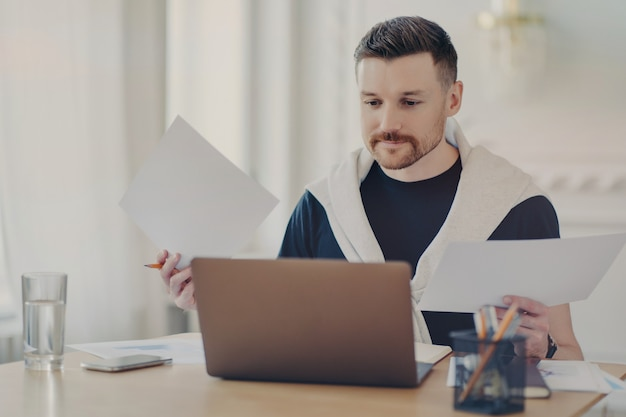 Busy male freelancer in casual clothes sitting at his workplace with computer and doing paperwork, analyzing project results while working remotely from home. freelance and business concept