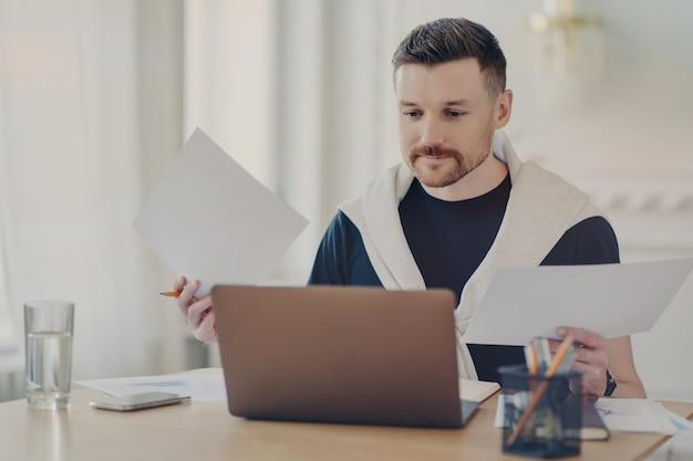 カジュアルな服装をした忙しい男性フリーランサーが、職場にコンピューターを持って座って事務処理を行い、自宅からリモートで仕事をしながらプロジェクトの結果を分析する。フリーランスとビジネス コンセプト