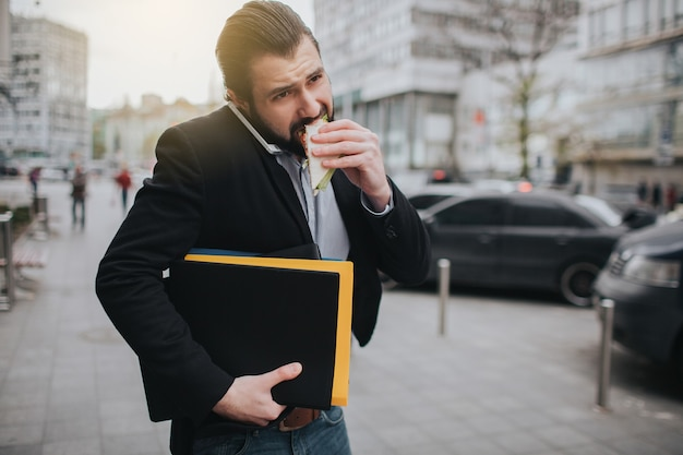 Busy man is in a hurry, he does not have time, he is going to eat snack on the go. worker eating, drinking coffee, talking on the phone, at the same time. businessman doing multiple tasks.