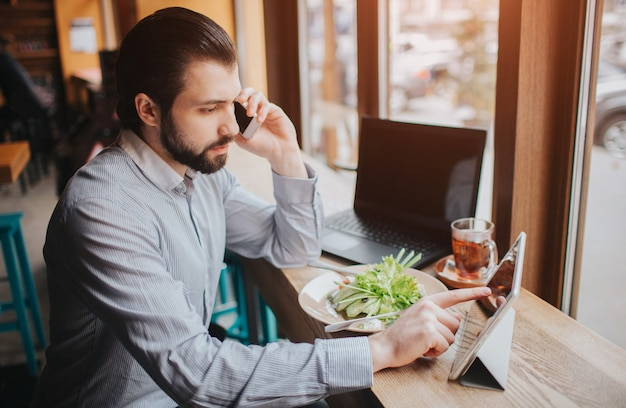 Busy man is in a hurry, he does not have time, he is going to eating and working. worker eating, drinking coffee, talking on the phone, at the same time. businessman doing multiple tasks.