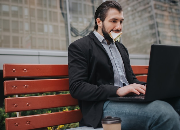 바쁜 남자는 서두르고 시간이 없어 야외에서 간식을 먹을 것입니다. 노트북에서 문서를 먹고 동시에 작업하는 작업자. 여러 작업을 수행하는 사업가.