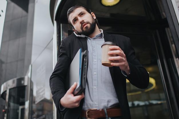 Занятый человек спешит, у него нет времени, он собирается разговаривать по телефону на ходу. бизнесмен делает несколько задач. многозадачность делового человека.