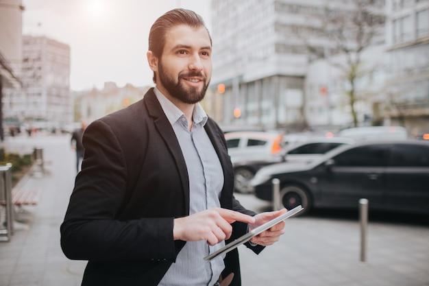 Занятый человек спешит, у него нет времени, он собирается использовать планшетный пк на ходу. бизнесмен делает несколько задач. многозадачность делового человека.