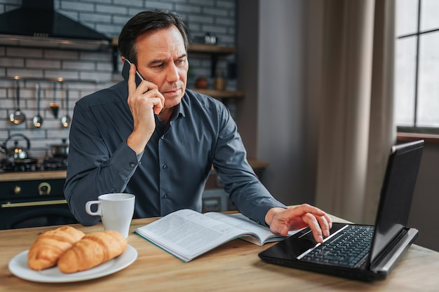 Busy man sit at table in kitchen and talk on phone. he type on keyboard laptop and work. journal white cup and plate with croissans on table.