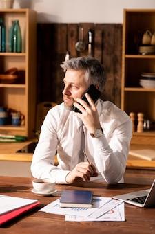 Занятой человек разговаривает по телефону на кухне