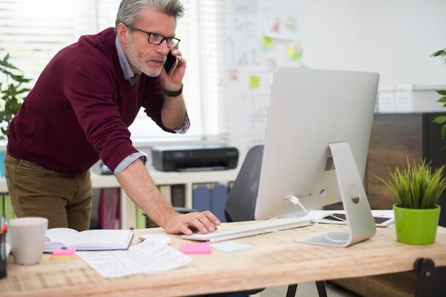 전화와 컴퓨터를 동시에 사용하는 바쁜 남자