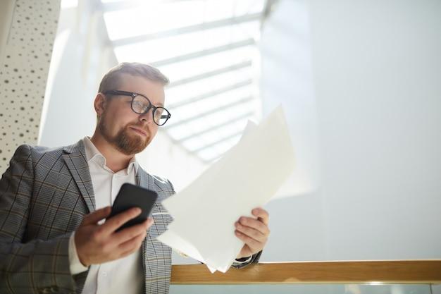Занятой человек, работающий с бумагами