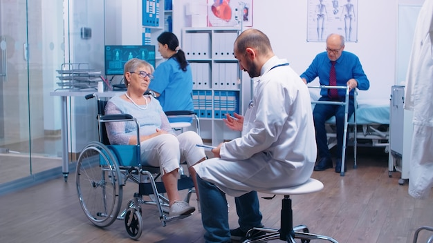 In busy modern private recovery clinic or hospital doctor is talking with disabled patient in wheelchair while nurse is bringing a man with walking disabilities in. health care medicine support assist