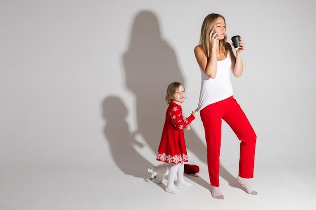 Занятая мама разговаривает по мобильному и пьет кофе, пока ее дочь в красном платье с рождественским узором тянет ее вверх, требуя внимания.