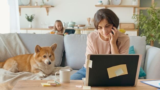 バックグラウンドで自宅から離れて仕事をしようとしている忙しいお母さんは、娘が机に座っている間...
