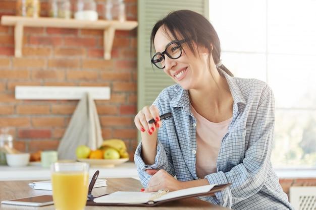 사업가의 바쁜 아침입니다. 나선 일기에 자신의 작업 일정을 적는 즐거운 웃는 여인이 긍정적 인 감정을 표현하고,