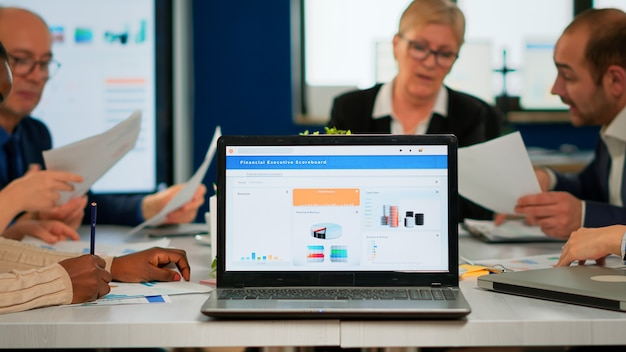 忙しい多文化の多様な従業員が、ビジネスソリューションを検索するドキュメントを保持しているラップトップの後ろにある会議デスクに座って年次財務統計を分析しています。会社で働くビジネスチーム
