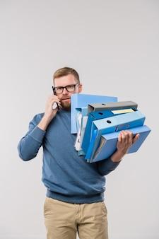 カメラの前でスマートフォンでクライアントに相談しながら、フォルダーのスタックを保持しているカジュアルウェアで忙しいオフィスマネージャー