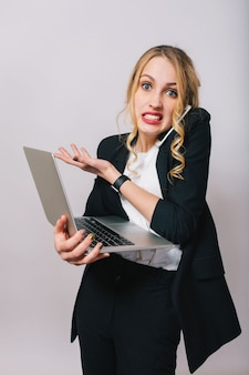 Busy office work time of astonished funny young blonde woman in white shirt and black jacket looking isolated. talking on phone, working with laptop, worker, job, manager