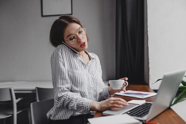 전화 통화 하 고 노트북에서 일하고, 차 한잔 들고 바쁜 회사원.