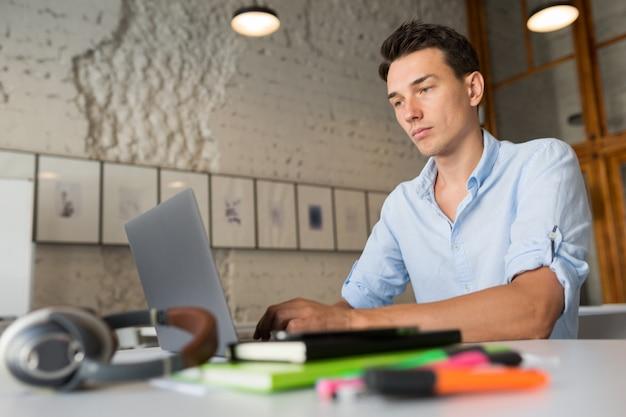 Занятый онлайн удаленный работник молодой уверенный в себе человек, работающий на ноутбуке