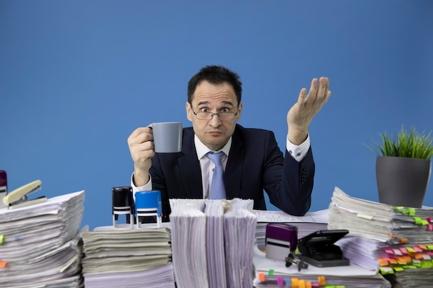 Busy overworked man wih cap of coffee sitting at table with pile of papers in office