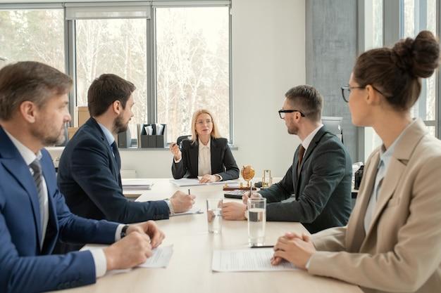 フォーマルなスーツを着てテーブルに座って上司の話を聞きながら会議で議題について話し合う法律事務所の忙しいパートナー