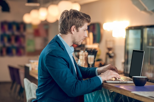 Busy person. profile of young serious man in business blue suit looking attentively at laptop while sitting with coffee in cafe