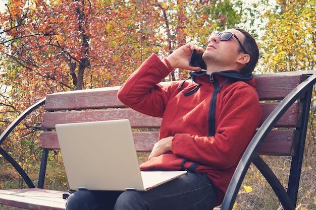 Занятый человек работает в сети вне офиса в отпуске. молодой человек, работающий на портативном компьютере в повседневной одежде. говоря по смартфону, сидя в парке. решение проблем по телефону. онлайн-бизнес.