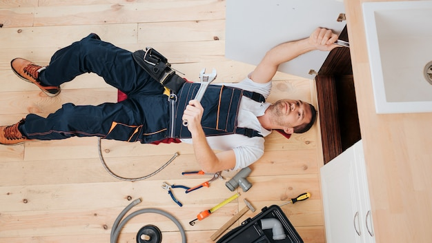 Busy plumber fixing on in kitchen under sink