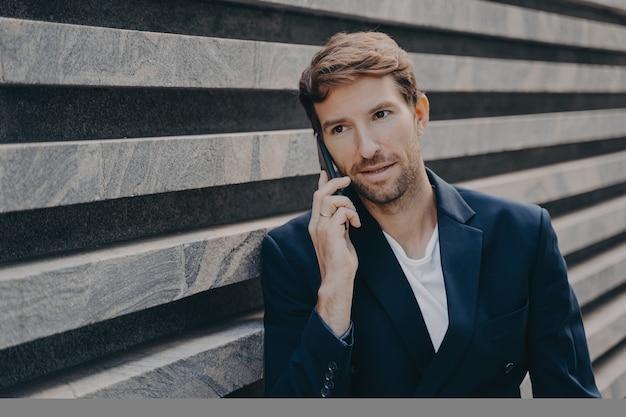 Занятый профессиональный предприниматель, сосредоточенный на расстоянии, носит официальную одежду и разговаривает по телефону
