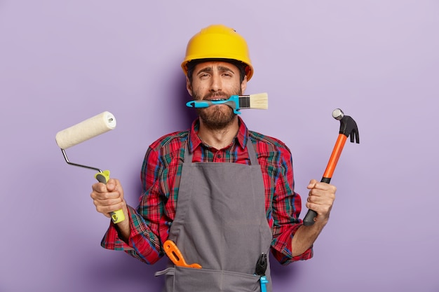 Busy repairman holds building tools, does repairing at home, wears yellow hardhat, apron, stands indoor.