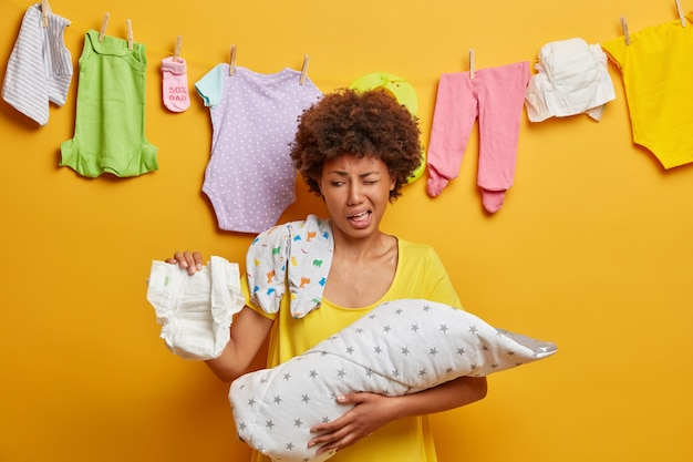 Busy responsible mother feels aversion as changes diaper, takes care of newborn and cleanliness, smells unpleasant stink, holds baby wrapped in blanket. parenting, family and nursing concept