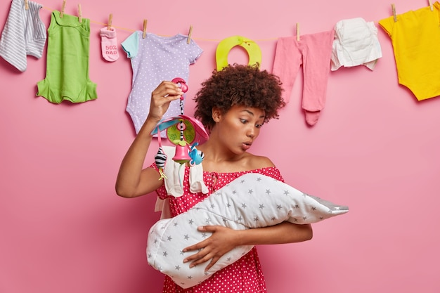 Busy responsible mother soothes crying baby, shows crib mobile, nursing newborn alone, comforts small daughter, has surprised expression. family bonding, bringing up, child care and motherhood concept
