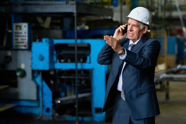 Busy senior entrepreneur using smartphone