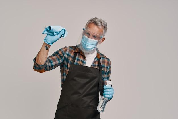 회색 배경에 서 있는 동안 앞치마와 얼굴 보호막 청소를 하는 바쁜 노인
