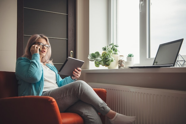 Busy senior woman with blonde hair and eyeglasses holding a tablet and talking on phone while working from home