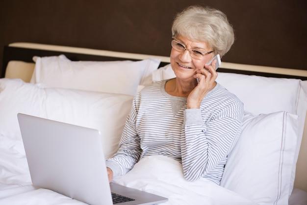 침대에서 일하는 바쁜 고위 여자