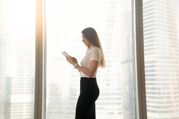 Busy serious businesswoman using digital tablet, standing near big window