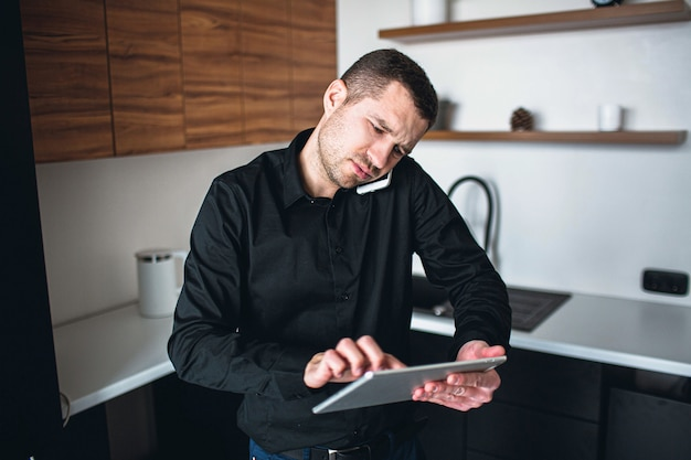 Busy serious young entrepreneur has phone call and use tablet for remote work. man stand in kitchen alone. businessman or company ceo has his own business.