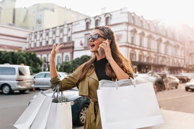 Donna maniaca dello shopping occupata con borse parlando al telefono e autobus in attesa in città