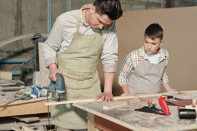 Busy skilled father in apron cutting wooden plank with jigsaw while his teenage son watching it in workshop