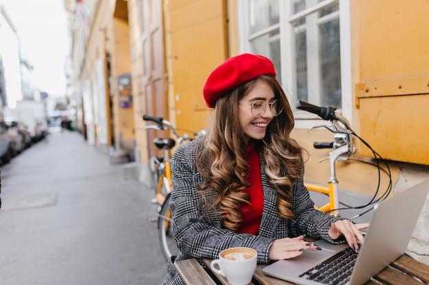 Занятая улыбающаяся женщина-фрилансер проводит время в летнем кафе