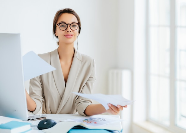 Busy successful female manager works with papers in office, poses at desktop, wears spectacles and formal outfit, busy preparing report, looks confidently