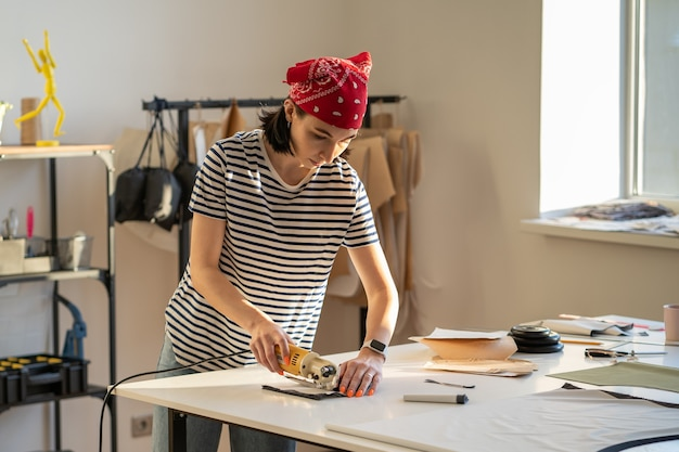 Занятый портной за работой в студии дизайнер женской одежды кроил ткань для шитья с помощью электрического резака
