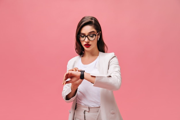 Busy woman in beige jacket looks at her hand watch. brunette with red bright lips in glasses and white headphones posing on isolated background.