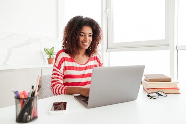 Busy woman in casual clothes working on laptop at home