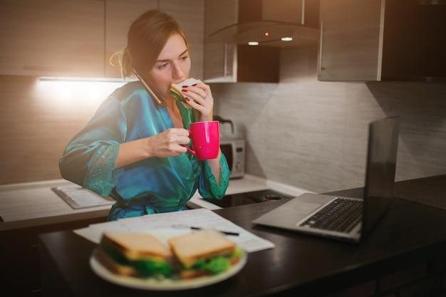 바쁜 여자가 먹고, 커피를 마시고, 전화로 이야기하고, 동시에 랩톱에서 작업